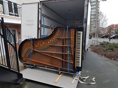 Pianotransport ev stor flygel på en flyttbil